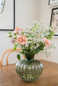 Flowers in green glass vase on dining table