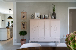 A white country-style highboard in front of a grey wall