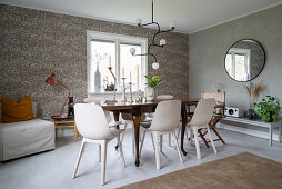 An antique wooden table with modern chairs in a dining room with papered walls