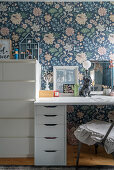 A desk and a chest of drawers in front of floral wallpaper