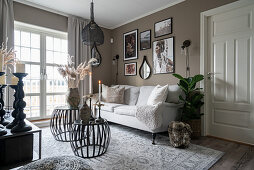 A sofa and coffee tables in a living room with a taupe wall