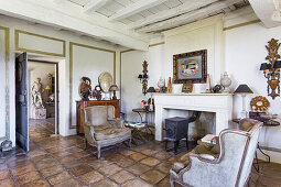 Cast iron stove and antique armchairs in interior room with tiled floor