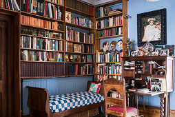 Framed artwork and desk with book-shelving in study