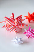 Origami 3D stars made from striped paper in shades of red