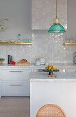 Kücheninsel mit Marmorplatte in weißer Küche mit glasierten Fliesen