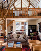 Double height living room with antique telescopes on mezzanine and suede armchairs in barn conversion