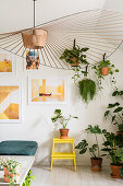 Designer lamp, many foliage plants and modern art on the wall in the living room