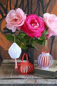 Selbstgemachte Lampions aus buntem Papier am Strauß mit Rosen