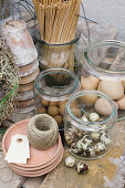 Jars of craft materials such as eggs, wooden spills, terracotta pots and twine