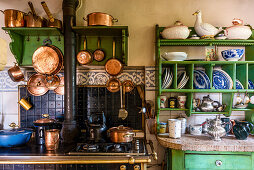 Rustic kitchen with hanging copper pans and plate rack