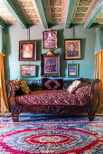 Antique sofa below gallery of paintings on green wall