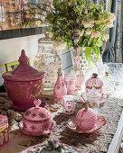 Pink crockery, sweet jars and flowers on table
