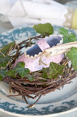 Homemade paper baby shoe in a nest as place cards