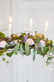 Chandelier with candles, ivy, eucalyptus, roses, and hyacinths