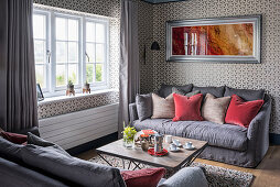 Two sofas facing one another in living room with graphic wallpaper
