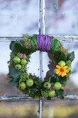Moss wreath with green apples, ivy leaves, and flowers