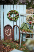 Autumn wreaths made of moss, ivy, onions, sedum, and snowberries, a heart made of snowberries in an old lantern