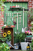 Garden tools, vegetables, sunflowers, rosemary stems, and basket with blossoms