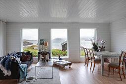 Sofa mit Couchtisch und Essbereich im Zimmer mit weiß lackierter Holzverkleidung