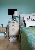 Bedroom with antique bedside cabinet and wall in turquoise