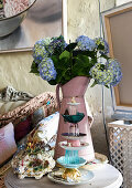 Cake stand made from stacked crockery in front of blue hydrangeas in metal jug