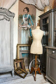 Tailors' dummy and gilt picture frames below portrait of woman holding a fish