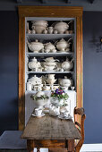 Wooden table and chair in front of shelves holding old white crockery