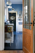 View through open door into blue-and-white, vintage-style kitchen