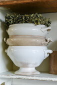 Stack of old soup tureens and wreath of dried flowers on shelf