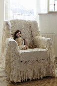 Doll on armchair with crocheted throw