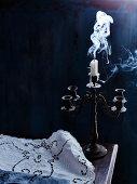 Smoking extinguished candle in vintage candelabra