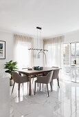 Upholstered chairs around wooden table in white, modern dining room