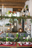 Weihnachtstisch und Regal mit Tannenzweigen und Blumen dekoriert