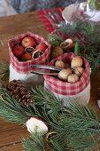 Nüsse und kleine Weihnachtsäpfel in Säckchen