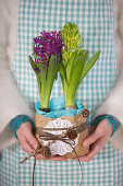 Hands hold hyacinths wrapped in parchment paper