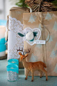 DIY Christmas wrapping with cake lace, deer figure and lanterns in the foreground