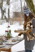 Frau verteilt Getränke am gedeckten Tisch im winterlichen Garten