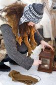 Frau stellt Teelicht in Vintage Laterne