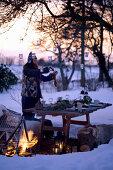 Frau hängt Laternen an Baum über gedecktem Tisch in verschneitem Garten