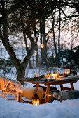 Hängende Laternen am Baum über gedecktem Tisch in verschneitem Garten