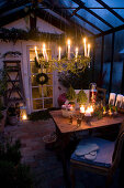Lit candles on wreath suspended above dining table in festively decorated conservatory