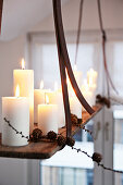 White pillar candles on suspended, DIY candle chandelier