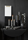 Lit candles and rolls of paper in containers on black console table
