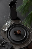 Black place setting decorated with conifer cones