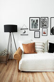 Black standard lamp next to rattan couch