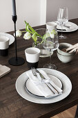 White place settings and tulips on wooden table