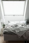 Bett mit Frühstücktablett unter Dachfenster