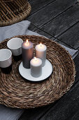 Lit candles and beakers on wicker tray