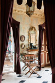 Antique directors chair in entrance hall with Roman plaster cameos and gilt-framed mirror
