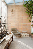 Leather chair in conservatory with terracotta wall tiles and model boat in foreground